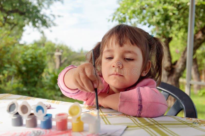 Το χαριτωμένο μικρό κορίτσι χρωματίζει τους ζωικούς αριθμούς στοκ φωτογραφίες