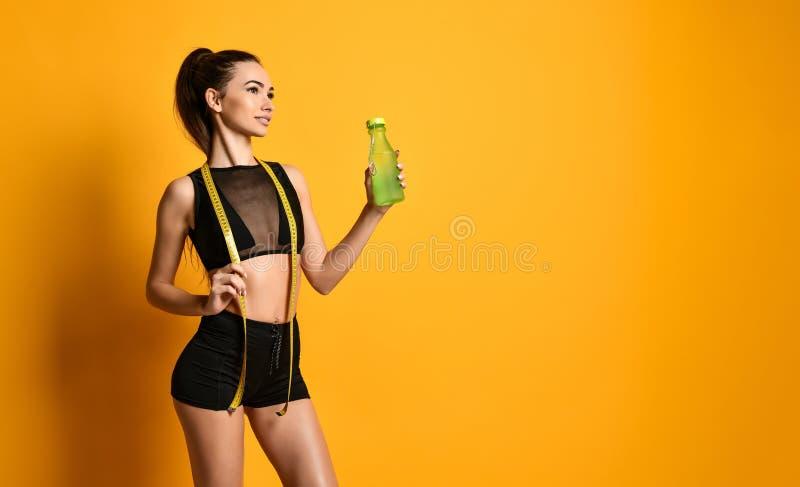 Το χαριτωμένο νέο κορίτσι ικανότητας στο μαύρο πουκάμισο εξετάζει τη κάμερα και κρατά τη μετρώντας ταινία και το νερό προσιτές στοκ φωτογραφίες με δικαίωμα ελεύθερης χρήσης