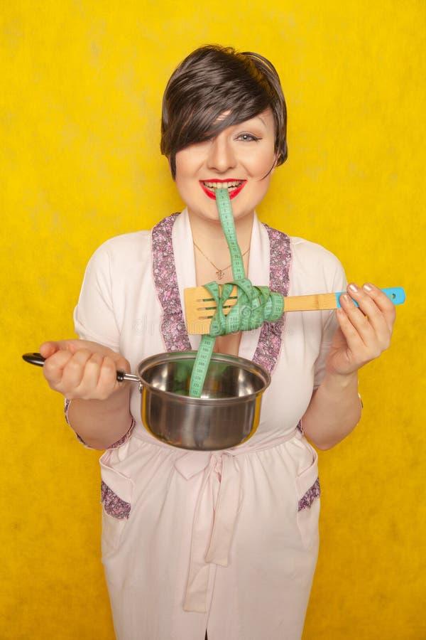 Το χαριτωμένο συναισθηματικό brunette είναι να λιμοκτονήσει, προσπαθώντας να ακολουθήσει μια διατροφή για την απώλεια βάρους μια  στοκ φωτογραφίες