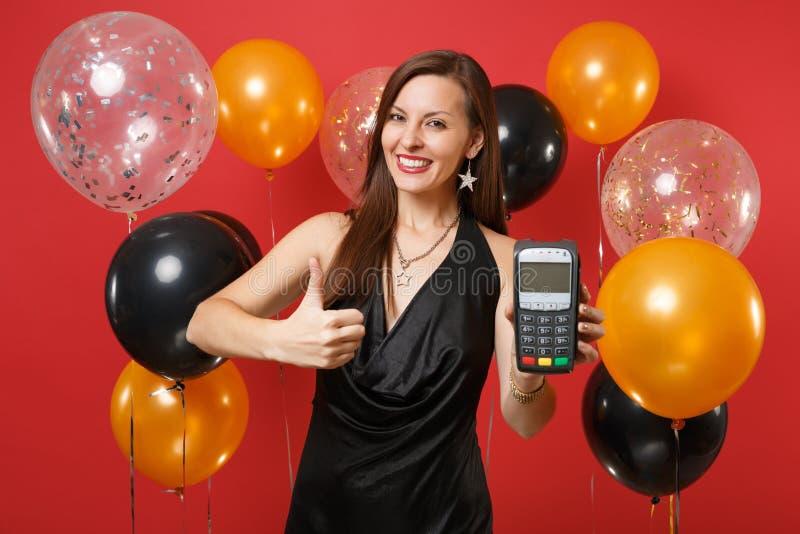 Το χαρούμενο κορίτσι στο μαύρο φόρεμα που κρατά το ασύρματο σύγχρονο τερματικό πληρωμής τραπεζών στη διαδικασία, αποκτά τις πληρω στοκ φωτογραφίες με δικαίωμα ελεύθερης χρήσης