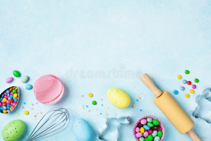 Το υπόβαθρο ψησίματος Πάσχας με την κυλώντας καρφίτσα, χτυπά ελαφρά, διακοσμητικά αυγά, κόπτες μπισκότων, καραμέλα και ζωηρόχρωμο στοκ εικόνα με δικαίωμα ελεύθερης χρήσης