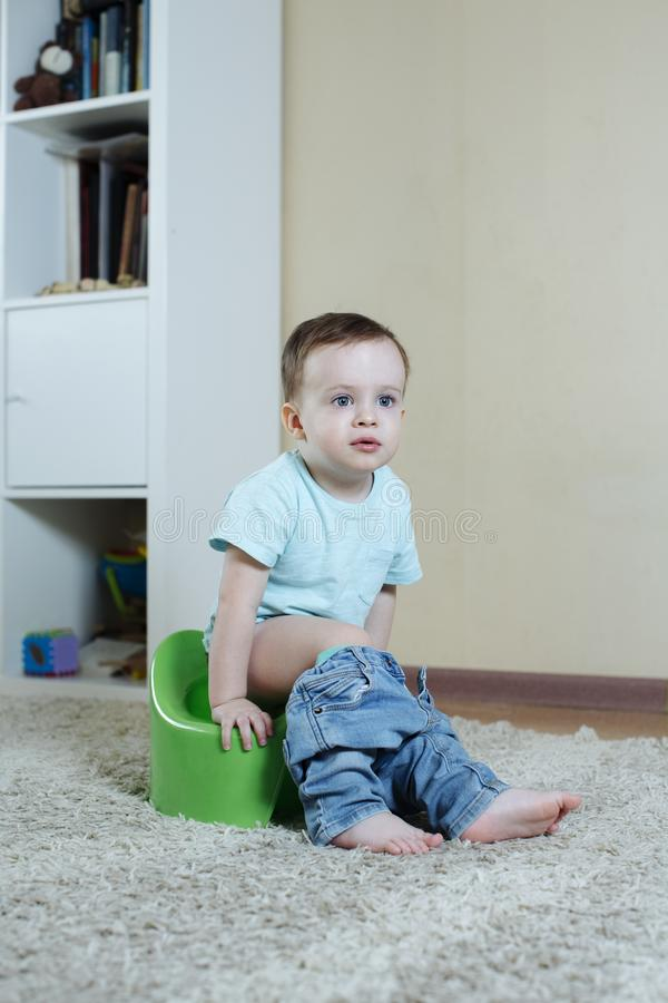 το παιδί κάθεται σε ένα δοχείο με τα τζιν κάτω και έγινε ενδιαφερόμενο σε κάτι στοκ φωτογραφία με δικαίωμα ελεύθερης χρήσης