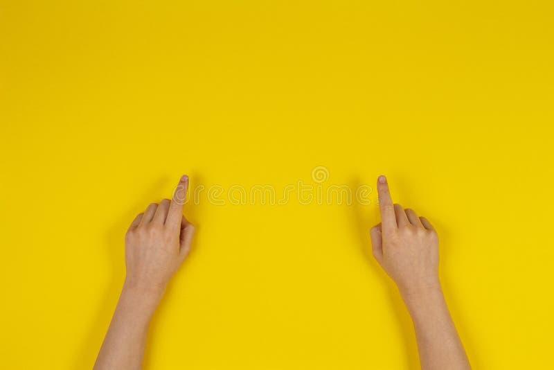Το παιδί δίνει τα δάχτυλα δείχνοντας στο κίτρινο υπόβαθρο στοκ εικόνες