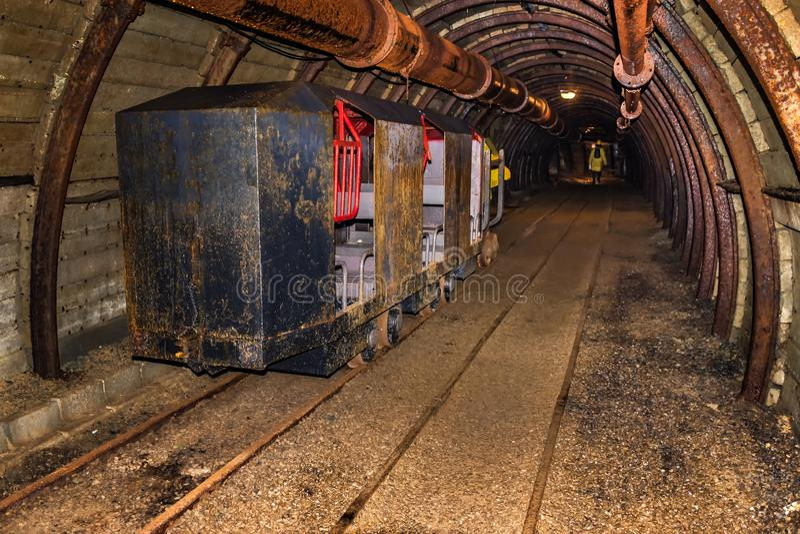 Το παλαιό και σκουριασμένο τραίνο ορυχείων για τη μεταφορά προσωπικού στάθμευσε στη σήραγγα ορυχείων με τον ξύλινο εφοδιασμό με ξ στοκ φωτογραφίες με δικαίωμα ελεύθερης χρήσης