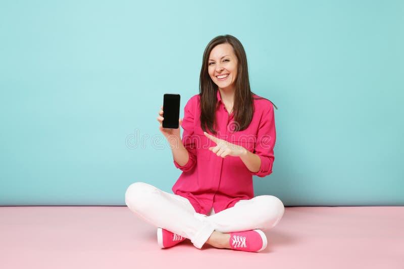 Το πλήρες πορτρέτο μήκους της νέας γυναίκας διασκέδασης στο ροδαλό πουκάμισο, άσπρα εσώρουχα κάθεται στο κινητό τηλέφωνο λαβής πα στοκ εικόνες με δικαίωμα ελεύθερης χρήσης