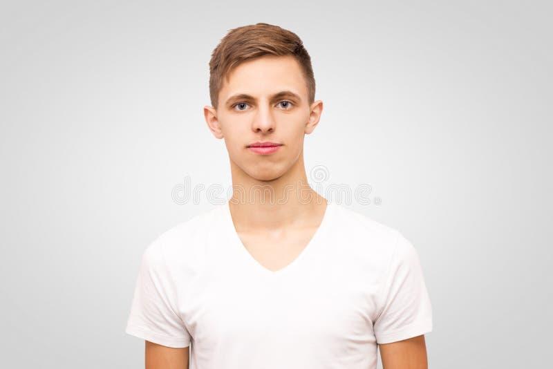 Το πορτρέτο ενός τύπου σε μια άσπρη μπλούζα, ηρεμεί το νεαρό άνδρα στοκ εικόνα