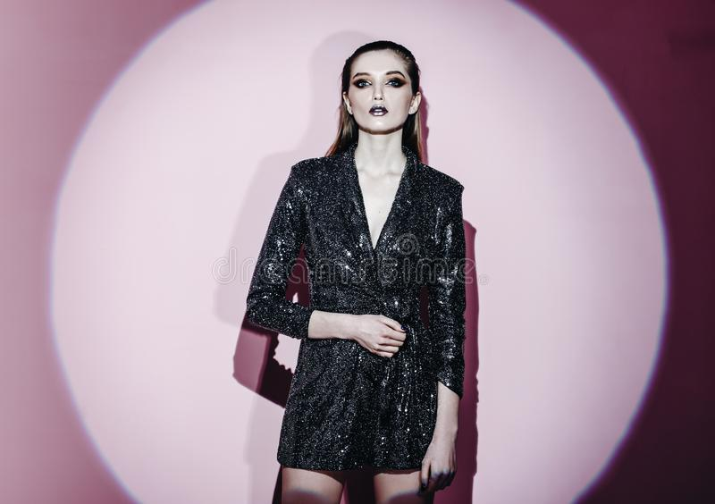 Το πορτρέτο μόδας του καθιερώνοντος τη μόδα κοριτσιού με την τρίχα τράβηξε πίσω και μοντέρνο makeup να λάμψει standin γ φορεμάτων στοκ εικόνες με δικαίωμα ελεύθερης χρήσης