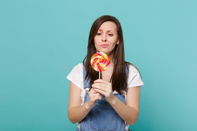 Το πορτρέτο μπερδεμένος η νέα γυναίκα στη λαβή ενδυμάτων τζιν, που κοιτάζει στο ζωηρόχρωμο κύκλο lollipop που απομονώθηκε στο μπλ στοκ εικόνα