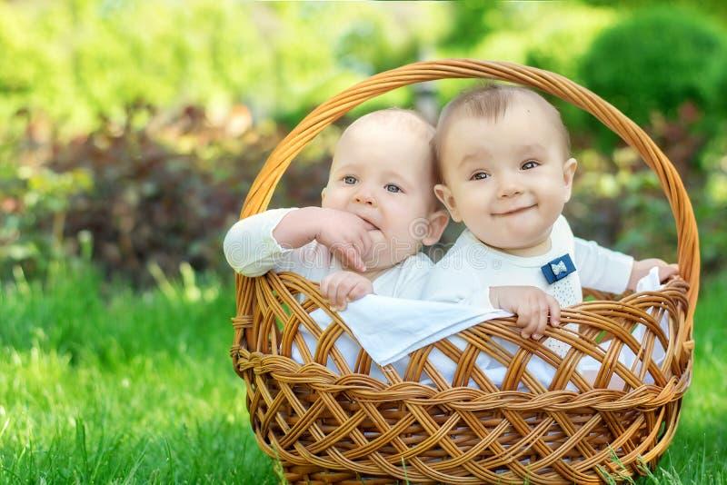 Το πορτρέτο δύο παιδιών νηπίων στα άσπρα κοστούμια κάθεται σε ένα καλάθι σε ένα πικ-νίκ υπαίθριο Το ξανθό παιδί είναι σοβαρό, το  στοκ φωτογραφία