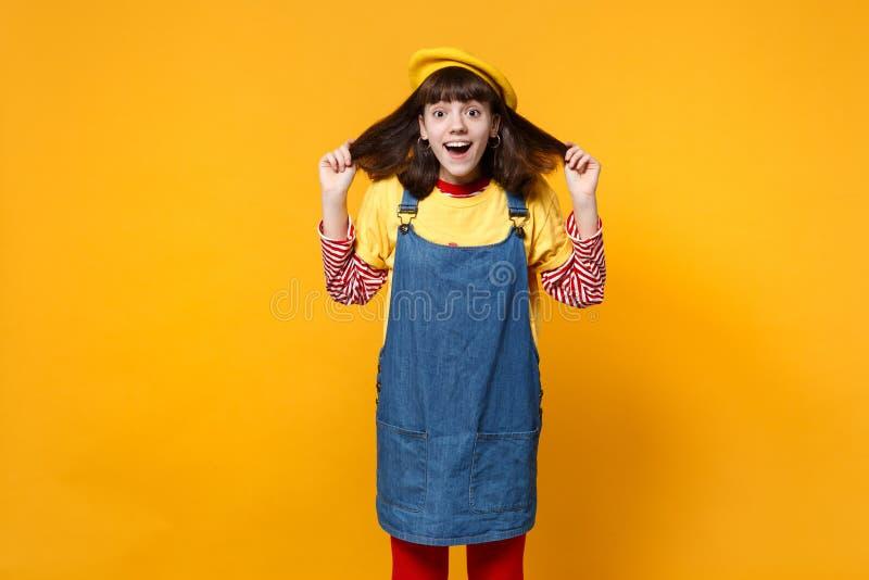 Το πορτρέτο του έκπληκτου εφήβου κοριτσιών γαλλικό beret, τρίχα εκμετάλλευσης τζιν sundress, που κρατά το στόμα ανοικτό απομόνωσε στοκ εικόνες