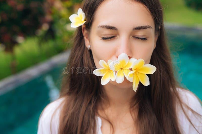 Το πορτρέτο του καλού κοριτσιού με τις ιδιαίτερες προσοχές και του plumeria, frangipani ανθίζει στο στοματικό υπόβαθρο λίμνης της στοκ φωτογραφία με δικαίωμα ελεύθερης χρήσης