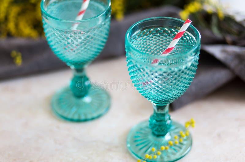 Το ποτό Refhesing μπλε εκλεκτής ποιότητας goblets στο άσπρο υπόβαθρο με ανθίζει στοκ εικόνα με δικαίωμα ελεύθερης χρήσης