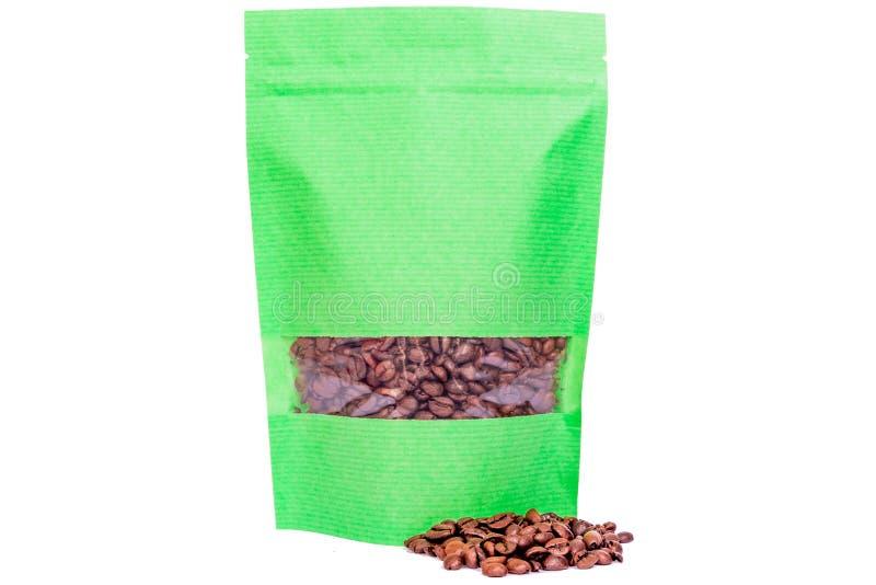 Το πράσινο γδυμένο έγγραφο doypack στέκεται επάνω τη σακούλα με το φερμουάρ παραθύρων που γεμίζουν με τα φασόλια καφέ στο άσπρο υ στοκ φωτογραφία με δικαίωμα ελεύθερης χρήσης
