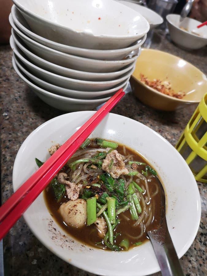 Το πρόστιμο έκοψε το νουντλς άσπρου ρυζιού πυκνώνει το κάλυμμα σούπας με τα τεμαχισμένα ταϊλανδικά τρόφιμα χοιρινού κρέατος και σ στοκ φωτογραφία
