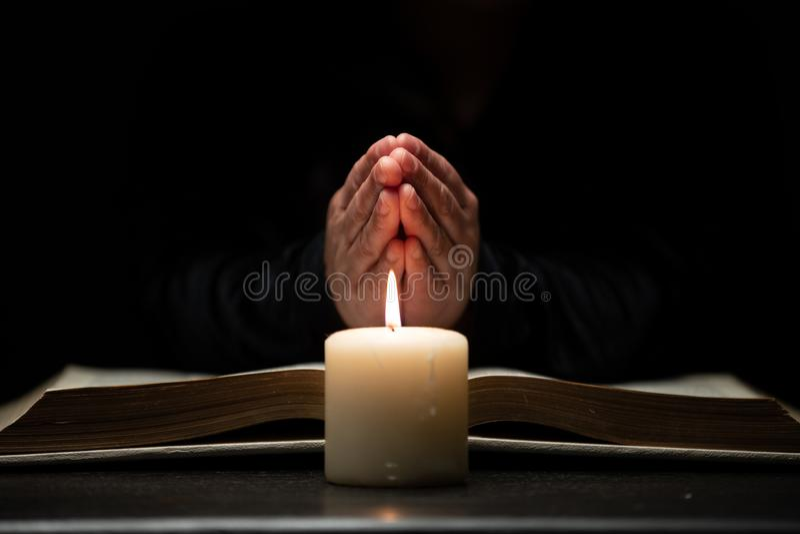 Το πρόσωπο που προσεύχεται με παραδίδει τη Βίβλο που φωτίζεται από το φως κεριών στοκ εικόνα με δικαίωμα ελεύθερης χρήσης