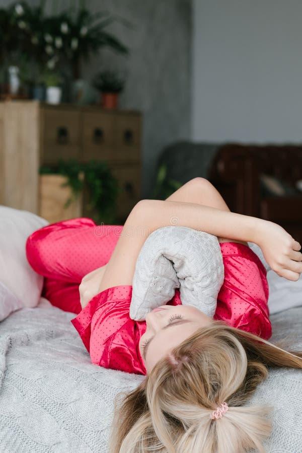 Το coziness πρωινού ξανθό το μαξιλάρι αγκαλιάσματος κρεβατιών στοκ φωτογραφίες με δικαίωμα ελεύθερης χρήσης