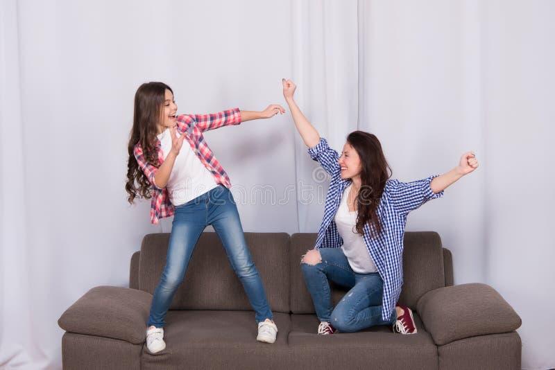 Το Mom και η κόρη κλείνουν τους φίλους Κοριτσίστικη ομάδα Μητέρα και εύθυμη κόρη που έχουν τη διασκέδαση στον καναπέ παιδική ηλικ στοκ εικόνες