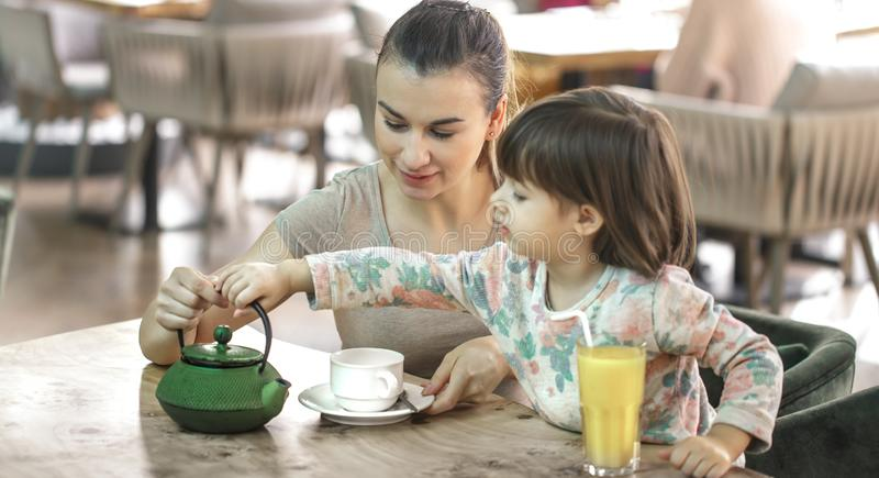 Το Mom και λίγη κόρη πίνουν το τσάι σε έναν καφέ στοκ εικόνα με δικαίωμα ελεύθερης χρήσης
