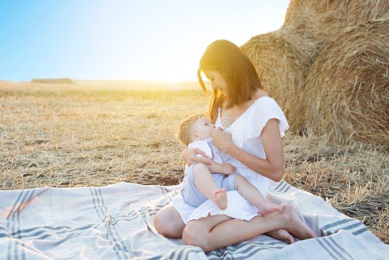 Το Mom περιποιείται το παιδί της στη φύση στοκ εικόνα με δικαίωμα ελεύθερης χρήσης