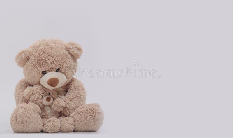 Το Mom teddy αντέχει τα αγκαλιάσματα απομονωμένο το γιος υπόβαθρό της στοκ εικόνες