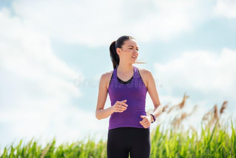 Τρέχοντας όμορφη νέα γυναίκα στο υπόβαθρο φύσης Σκληρές workout και ασκήσεις στοκ εικόνες