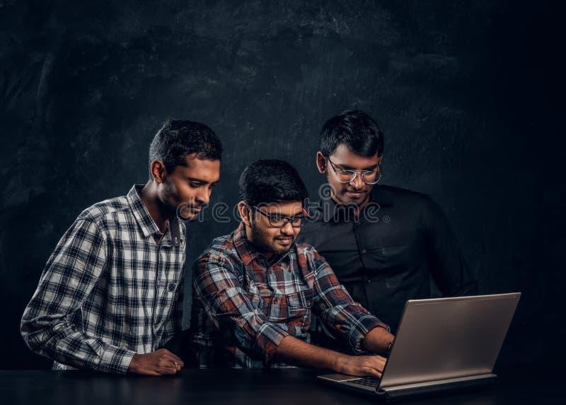 Τρία σκοτεινός-ξεφλουδισμένος τύπος που κουβεντιάζει σε ένα lap-top στοκ εικόνες