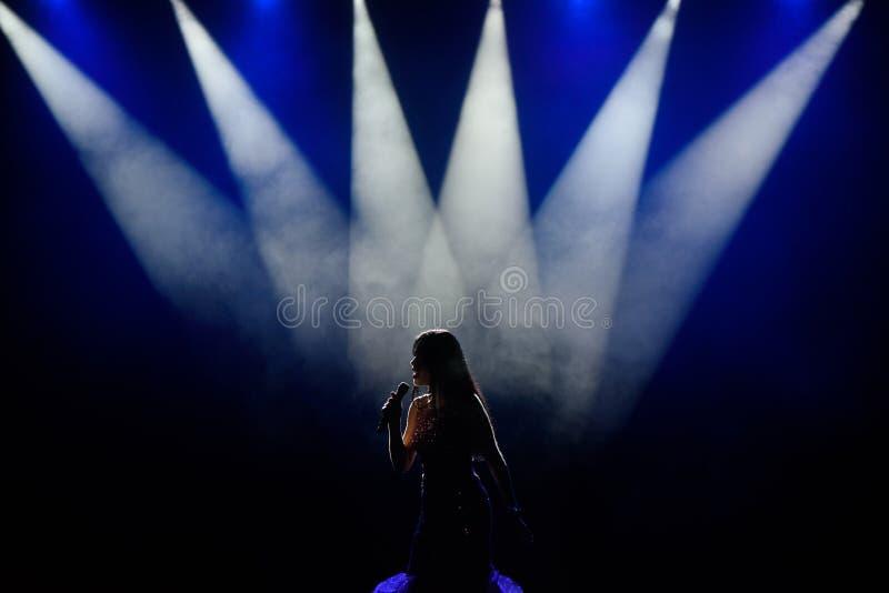 Τραγουδιστής στη σκιαγραφία Ένας νέος τραγουδιστής γυναικών στη σκηνή κατά τη διάρκεια μιας συναυλίας στοκ εικόνες