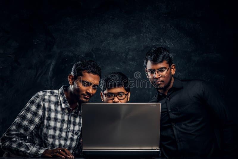 Τρεις ινδικοί σπουδαστές που εργάζονται σε ένα πρόγραμμα που στέκεται μαζί στον πίνακα με ένα lap-top στοκ φωτογραφία