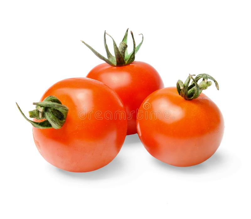 Τρεις κόκκινες ντομάτες κερασιών με τις πράσινες ακίδες σε ένα απομονωμένο λευκό υπόβαθρο Κινηματογράφηση σε πρώτο πλάνο στοκ εικόνα