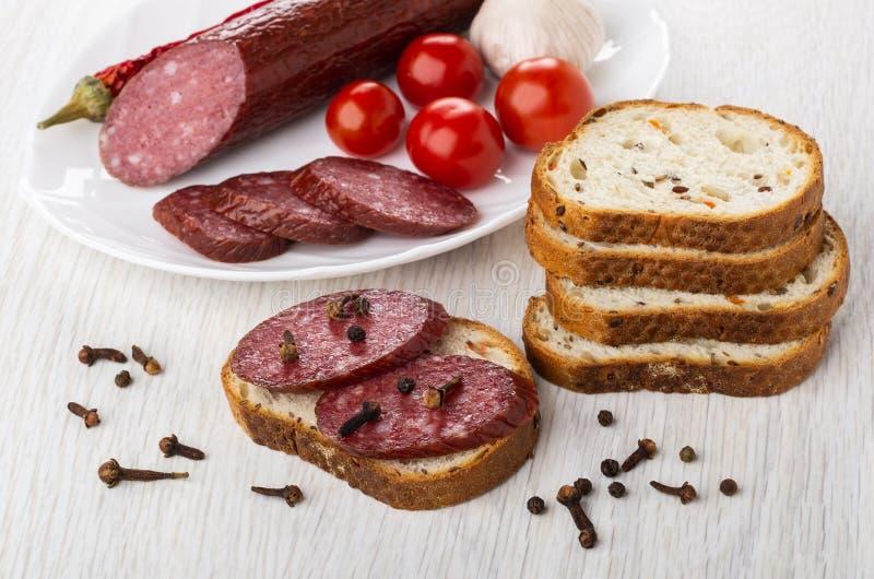 Φέτες του καπνισμένου λουκάνικου, σκόρδο, πιπέρι τσίλι, ντομάτες στο πιάτο, σάντουιτς με το λουκάνικο, μαύρο πιπέρι, καρύκευμα γα στοκ φωτογραφία με δικαίωμα ελεύθερης χρήσης