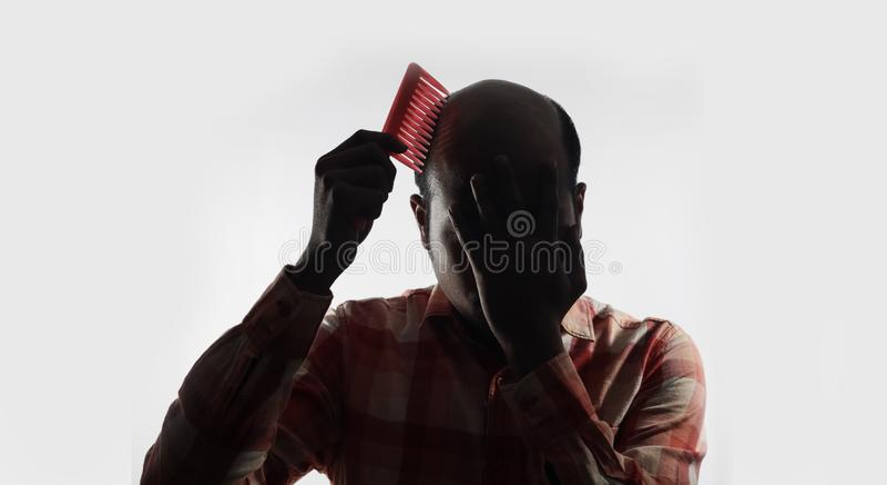 Φαλακρό άτομο που καλύπτει το πρόσωπό του και που κτενίζει στο άσπρο υπόβαθρο με το διάστημα για το κείμενο στοκ εικόνα με δικαίωμα ελεύθερης χρήσης