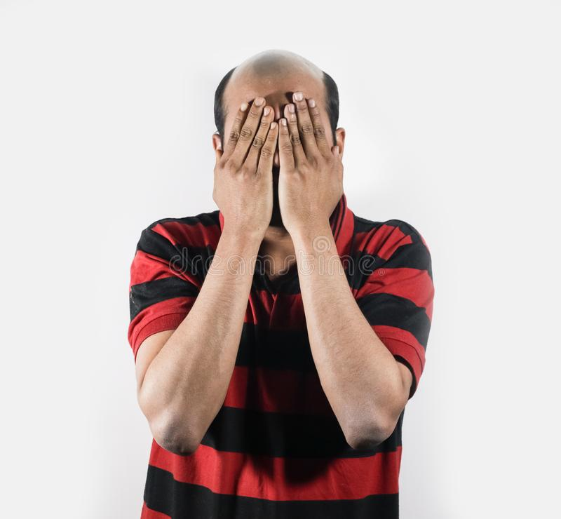 Φαλακρό άτομο που καλύπτει το πρόσωπό του στην ντροπή στο άσπρο υπόβαθρο με το διάστημα για το κείμενο στοκ εικόνες