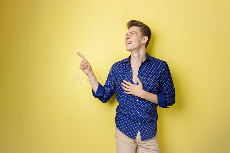 Φιλικό να φανεί εύθυμος ευρωπαϊκός τύπος με τη σκοτεινή τρίχα που φορά το μπλε πουκάμισο, χαμογελώντας ευρέως, που δείχνει αριστε στοκ εικόνες