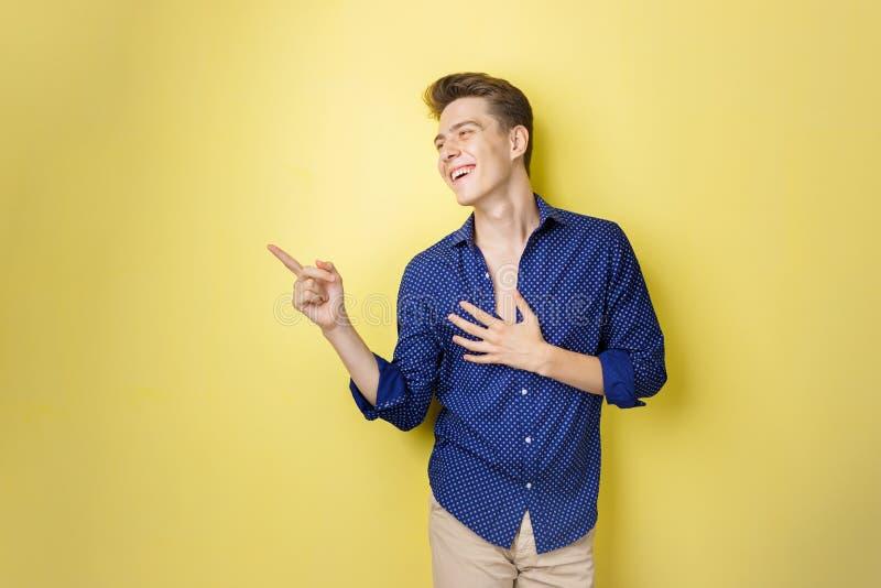 Φιλικό να φανεί εύθυμος ευρωπαϊκός τύπος με τη σκοτεινή τρίχα που φορά το μπλε πουκάμισο, χαμογελώντας ευρέως, που δείχνει αριστε στοκ εικόνα με δικαίωμα ελεύθερης χρήσης