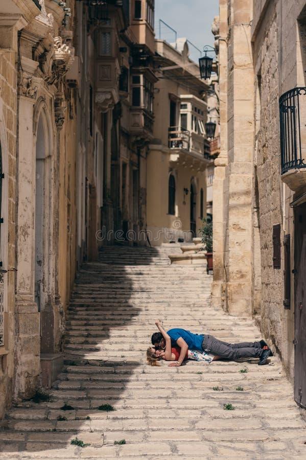 Φιλώντας γυναίκα ανδρών που βάζει στα σκαλοπάτια στην οδό στοκ φωτογραφία με δικαίωμα ελεύθερης χρήσης