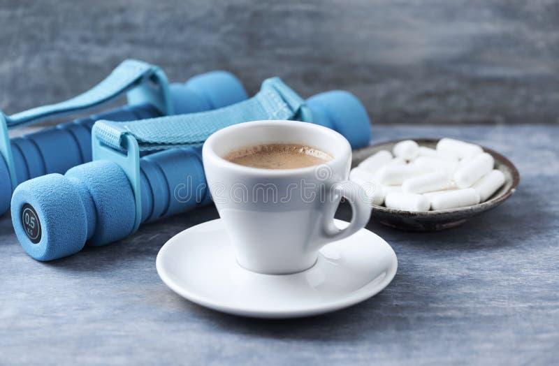 Φλιτζάνι του καφέ, αλτήρες και κάψες βήτα-αλανινών στο μπλε ξύλινο υπόβαθρο στοκ εικόνα με δικαίωμα ελεύθερης χρήσης