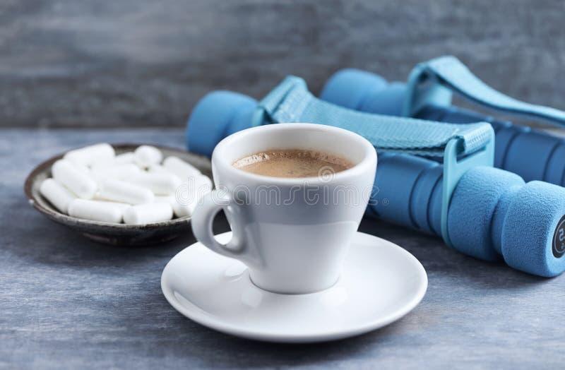 Φλιτζάνι του καφέ, αλτήρες και κάψες βήτα-αλανινών στο μπλε ξύλινο υπόβαθρο στοκ φωτογραφία