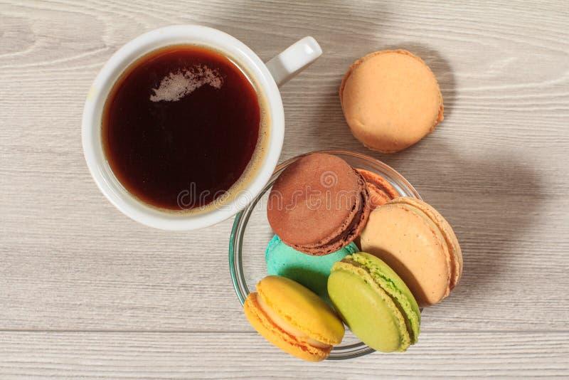 Φλιτζάνι του καφέ και εύγευστα κέικ macarons του διαφορετικού χρώματος στο κύπελλο γυαλιού στοκ φωτογραφία με δικαίωμα ελεύθερης χρήσης