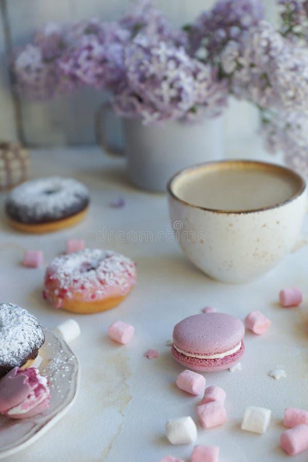 Φλυτζάνι του cappuccino, των φρέσκων ζωηρόχρωμων donuts, της φράουλας macarons και της ανθοδέσμης της πασχαλιάς στον άσπρο μαρμάρ στοκ φωτογραφίες με δικαίωμα ελεύθερης χρήσης