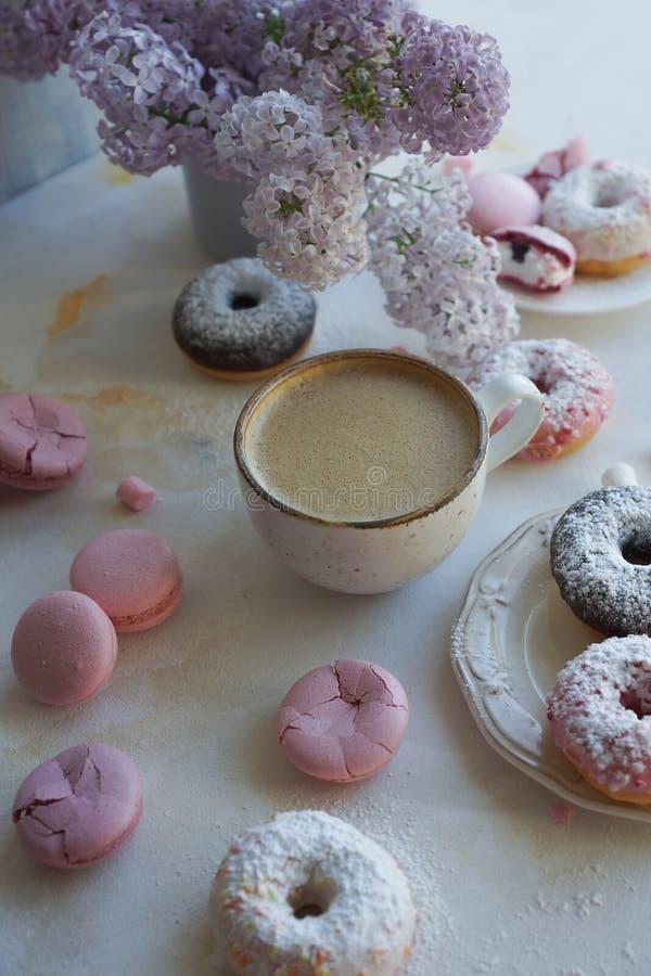 Φλυτζάνι του cappuccino, των φρέσκων ζωηρόχρωμων donuts, της φράουλας macarons και της ανθοδέσμης της πασχαλιάς στον άσπρο μαρμάρ στοκ εικόνες