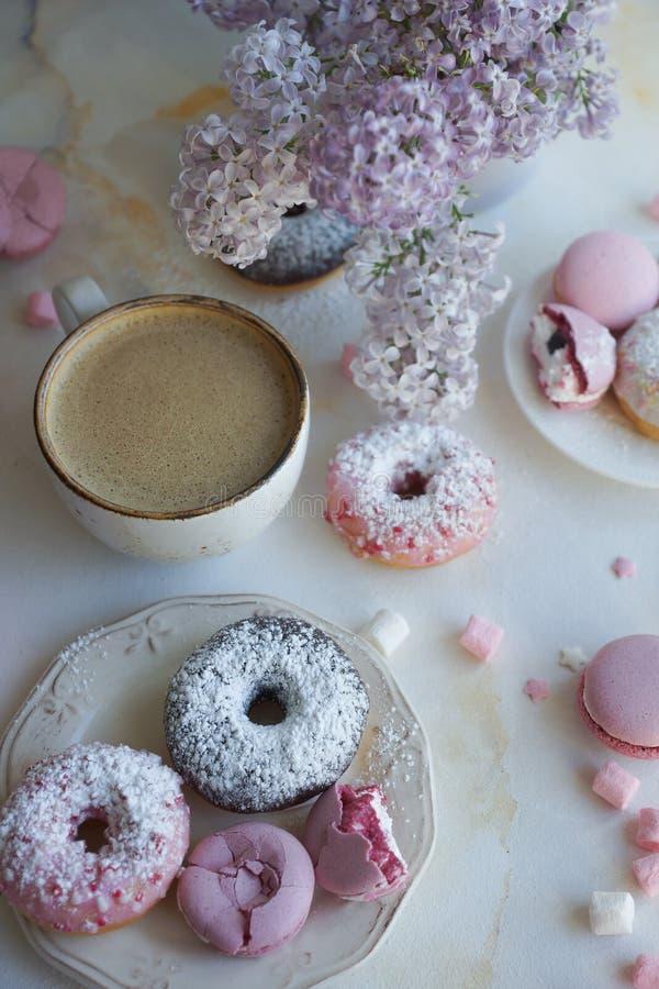Φλυτζάνι του cappuccino, των φρέσκων ζωηρόχρωμων donuts, της φράουλας macarons και της ανθοδέσμης της πασχαλιάς στον άσπρο μαρμάρ στοκ φωτογραφία με δικαίωμα ελεύθερης χρήσης
