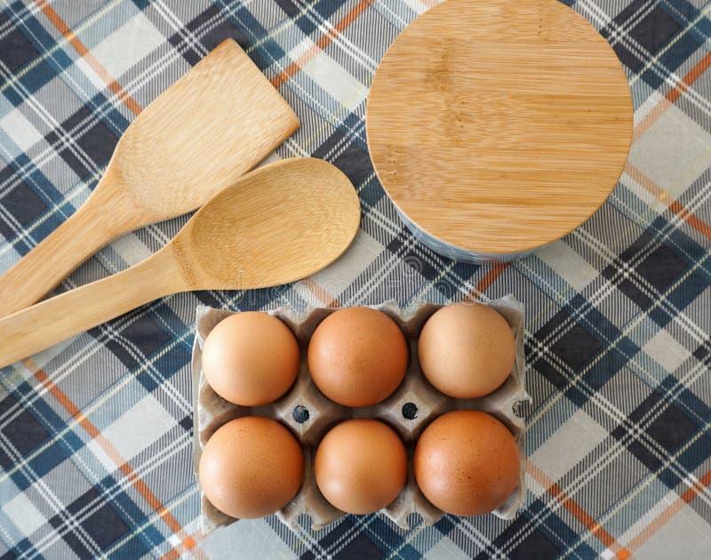 Φρέσκα ακατέργαστα αυγά κοτόπουλου στο κιβώτιο αυγών, τα ξύλινα κουτάλια και το εμπορευματοκιβώτιο για το αλεύρι ή τη ζάχαρη στοκ φωτογραφίες με δικαίωμα ελεύθερης χρήσης