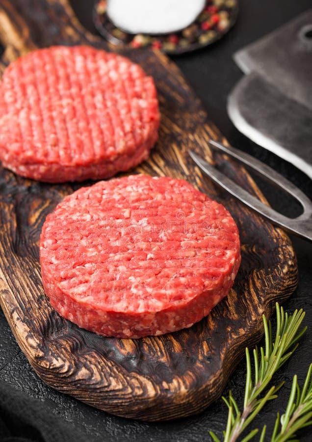 Φρέσκα ακατέργαστα κομματιασμένα σπιτικά burgers βόειου κρέατος σχαρών αγροτών στον εκλεκτής ποιότητας τεμαχίζοντας πίνακα με τα  στοκ εικόνα με δικαίωμα ελεύθερης χρήσης