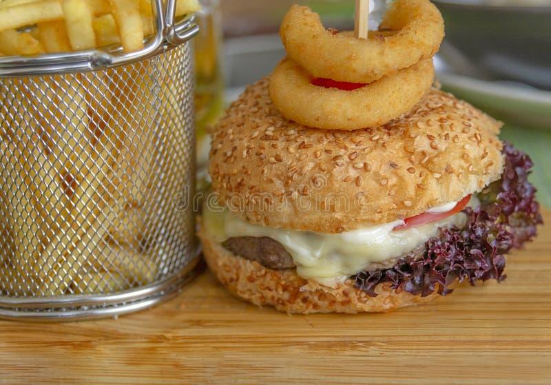 Φρέσκα νόστιμα burger και τηγανητά με τα δαχτυλίδια κρεμμυδιών στον ξύλινο πίνακα στοκ εικόνες