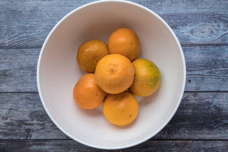 Φρέσκα πορτοκάλια στο άσπρο κύπελλο στο ξύλινο επιτραπέζιο υπόβαθρο στοκ εικόνα