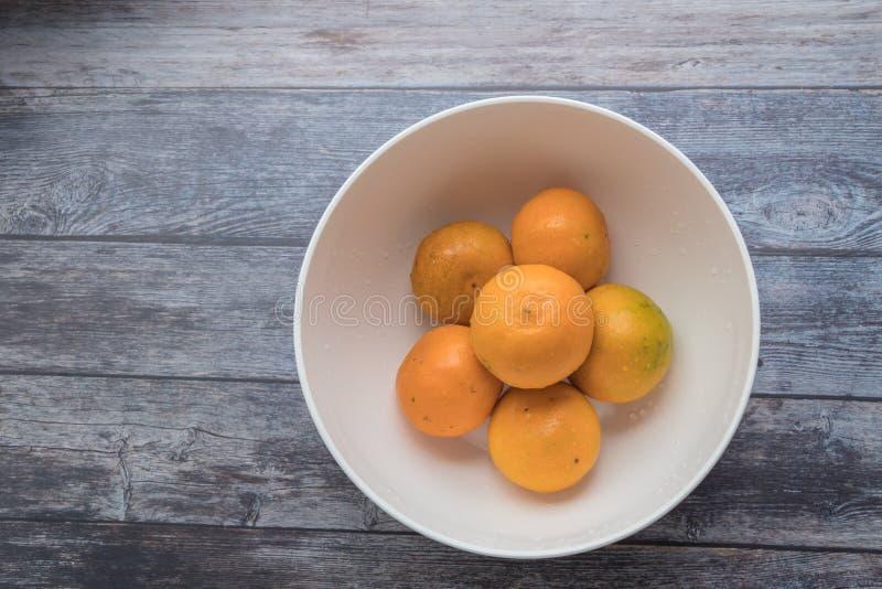 Φρέσκα πορτοκάλια στο άσπρο κύπελλο στο ξύλινο επιτραπέζιο υπόβαθρο στοκ εικόνες
