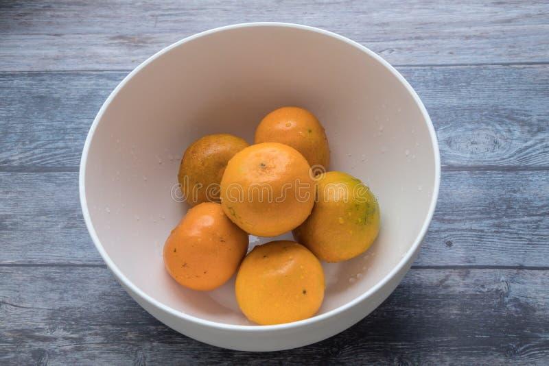 Φρέσκα πορτοκάλια στο άσπρο κύπελλο στο ξύλινο επιτραπέζιο υπόβαθρο στοκ εικόνα με δικαίωμα ελεύθερης χρήσης