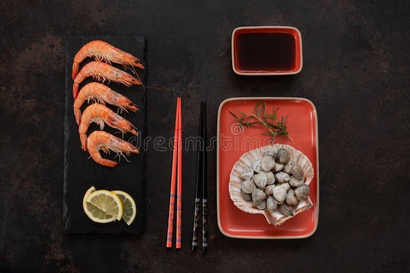 Φρέσκες γαρίδες στη μαύρη γέφυρα πετρών με το λεμόνι και ακατέργαστο gallina chamelea μαλακίων κυματωγών στο κοχύλι οστράκων στο  στοκ φωτογραφία