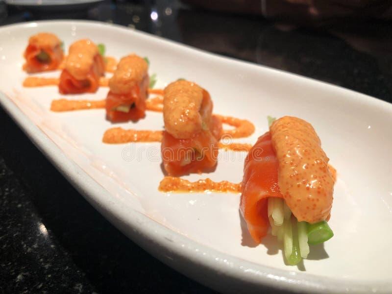 Φρέσκος ρόλος σολομών με το σπαράγγι και αγγούρι που ολοκληρώνεται με τη σάλτσα αυγοτάραχων σολομών στο άσπρο πιάτο στοκ εικόνες