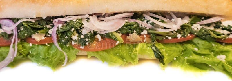 Φρέσκο γαλλικό σάντουιτς baguette με τις ντομάτες και το σπανάκι τυριών κρεμμυδιών, στο άσπρο πιάτο στοκ φωτογραφία